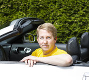 Mature man with arms on top of convertible car door Royalty Free Stock Photos