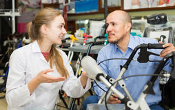 Mature man asking doctor about wheelchairs. Mature men asking doctor about wheelchairs in store Royalty Free Stock Photos