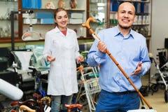 Mature man asking positive female doctor about walking sticks stock image