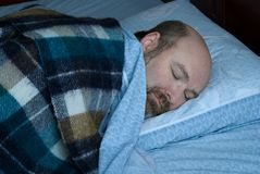 Mature man asleep. Middle aged man, bald with beard, peacefully asleep on side. subdued lighting with blue cast suggesting night stock photo