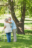 Mature man assisting woman with walker at park Royalty Free Stock Photos