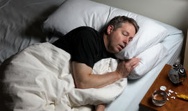 Mature man attempting to fall asleep after taking medicine. Mature man resting head in pillow while trying to sleep in bed. Insomnia concept with pain medicine Royalty Free Stock Image