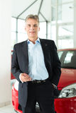 Mature man with auto in car dealership Stock Photos