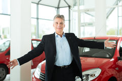 Mature man with auto in car dealership Royalty Free Stock Image