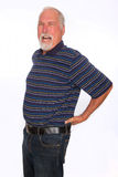 Mature man with back pain. A mature man yelling in pain as he holds his lower back royalty free stock images