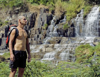 Mature man with backpack at waterfall pongour Royalty Free Stock Photo