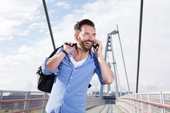 Mature man with bag talking on mobile phone and laughing Royalty Free Stock Photos