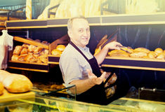 Mature man baker offering fresh baguettes and buns. In bakery Stock Images