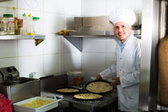 Mature man baking pizza in restaurant Stock Image
