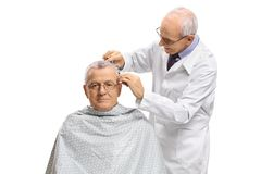 Mature man with a barber cutting his hair. Mature men with a barber cutting his hair isolated on white background Royalty Free Stock Image