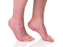 Mature man barefoot with dry skin. And nails standing on tips of toes isolated on white background stock images
