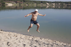 Mature man in a baseball cap and bathing shorts jumping on a san. Dy beach near the blue lake Royalty Free Stock Images