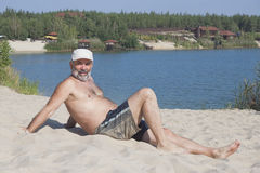 Mature man in a baseball cap and bathing shorts lying on a sandy Royalty Free Stock Image