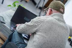 Mature man with  baseball cap using a laptop, back view Stock Photography