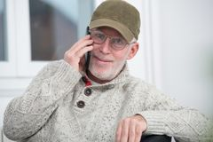 Mature man with  baseball cap using a smartphone Royalty Free Stock Photos