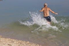 Mature man in bathing shorts running into the blue lake swim Royalty Free Stock Photos