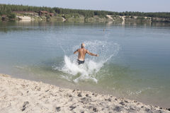 Mature man in bathing shorts running into the blue lake swim Royalty Free Stock Images