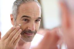 Mature man in bathroom applying cream. Mature man in front of mirror applying cosmetics royalty free stock photos