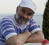 A mature man with a beard. Wearing a cap smiling Royalty Free Stock Photography