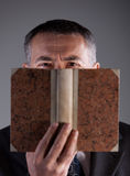 Mature man behind an ancient book Stock Photography