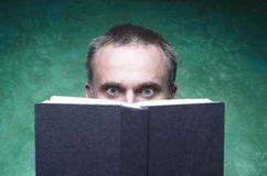 Mature man being focused and hooked by book, reading open book, surprised young man, amazing eyes looking blank cover, green backg Stock Images
