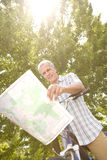 Mature man with bicycle reading map, low angle view (sun flare) stock images