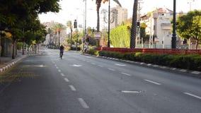 Mature man bikes on car-less road stock footage
