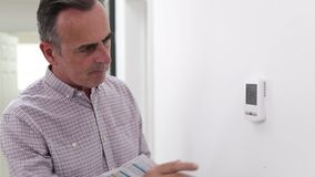 Mature man with bill turning down central heating thermostat stock video