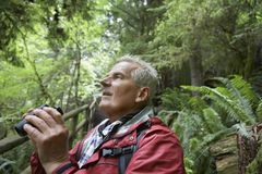 Mature Man With binoculars In Forest Royalty Free Stock Photography