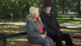Mature man sits near woman at the park. Mature man in black coat and hat sits near woman at the bench at the park. Old people are flirting. Tall man and short stock video