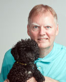 Mature man with black poodle Royalty Free Stock Image