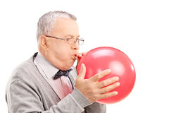 Mature man blowing up a balloon Royalty Free Stock Images