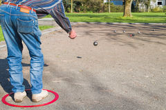 Mature man in blue jeans playing boule in park Royalty Free Stock Photography