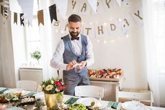 Mature man with bow and vest setting a table for an indoor party. royalty free stock photo