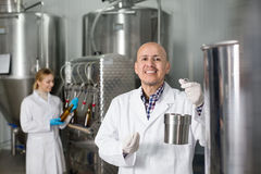 Mature man among brewery equipment. Mature cheerful experienced men wearing uniform standing among a brewery stainless equipment Royalty Free Stock Photography
