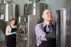 Mature man among brewery equipment. Mature cheerful men wearing a uniform standing among a brewery stainless equipment Stock Photos