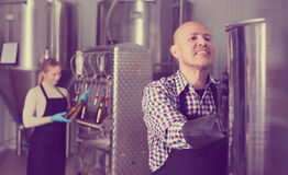 Mature man among brewery equipment. Mature cheerful men wearing a uniform standing among a brewery stainless equipment Royalty Free Stock Photography