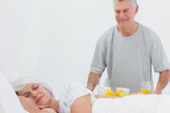 Mature man bringing sleeping wife breakfast in bed. Mature men bringing sleeping wife breakfast in bed with orange juice and fruits Stock Photo