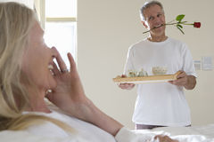 Mature man bringing wife breakfast in bed, carrying tray, holding single red rose between teeth Stock Image
