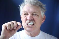 Mature man brushes teeth Royalty Free Stock Photos