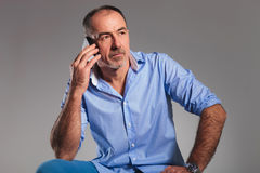 Mature man calling on his telephone while looking away Stock Photo