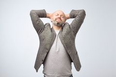 Portrait of cute unshaven adult yawning, being exhausted after work. Mature man came from night club or hard work and needs some sleep. Portrait of cute stock photography