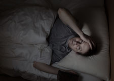 Mature man cannot fall asleep during night time. Top view image of mature man, looking forward, having trouble sleeping from insomnia Stock Photography