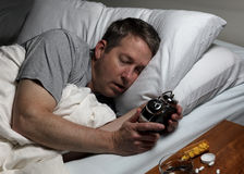 Mature man cannot fall asleep thus looking at time on alarm clock. Mature man holding and staring at alarm clock while trying to fall asleep. Insomnia concept royalty free stock photography
