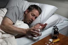 Mature man cannot fall asleep thus preparing to take medicine. Mature man holding medicine and a glass of water while trying to fall asleep. Insomnia concept Stock Images