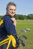 Mature Man Carrying a Golf Bag. A handsome senior carrying a golf bag on a driving range Royalty Free Stock Image
