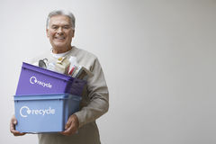 Mature Man Carrying Recycling Bin Stock Photography