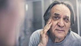 Mature man checking his wrinkles. Mature man checking his  wrinkles stock photo
