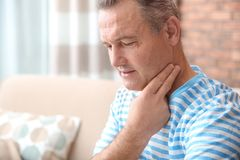 Mature man checking pulse with fingers at home royalty free stock photos