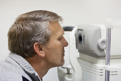 Mature man checks sight. On the special device Stock Photo